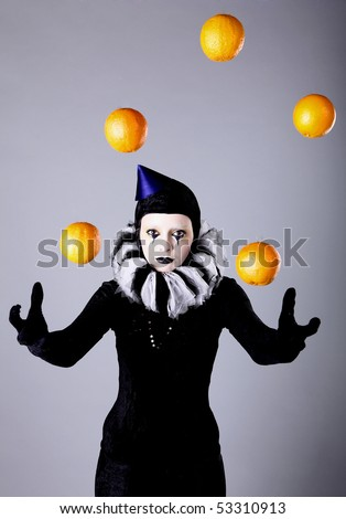Circus fashion mime juggles with five oranges. Photo. - stock photo