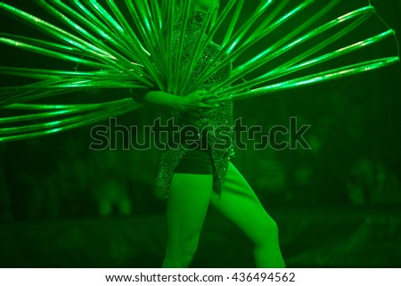 Circus performance concept. Dancing woman rotates big number of hula hoops in show watchers background. Green color circus illumination. Indoor shot