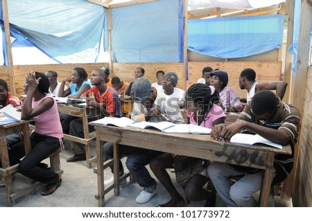 CITE SOLEIL- AUGUST 25:  Students of all ages attending classes in a local community school in Cit�© Soleil- one of the poorest area in the Western Hemisphere on August 25 2010 in Cite Soleil, Haiti. - stock photo