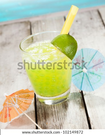 Citrus Boba Tea with bubbles and two paper cocktail umbrella in front of a swimming pool - stock photo