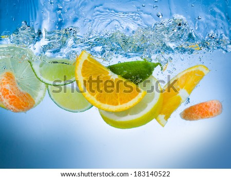 Citrus fruit dropping into water with a big splash. - stock photo