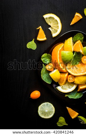 Citrus fruit salad on black background. Fruit dessert. Top view, flat lay - stock photo
