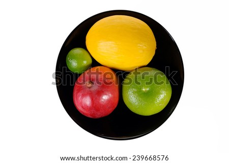 Citrus fruits in a black bowl isolated on white background - stock photo