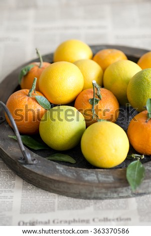 Citrus fruits in a wooden tray - stock photo