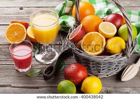 Citrus fruits in basket and juice glasses. Orange, lemon, lime. - stock photo