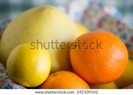 Citrus fruits include pomelo, lime, and orange are mix in a closeup view.