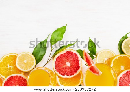 Citrus fruits slice with green leaves on white wooden background, frame