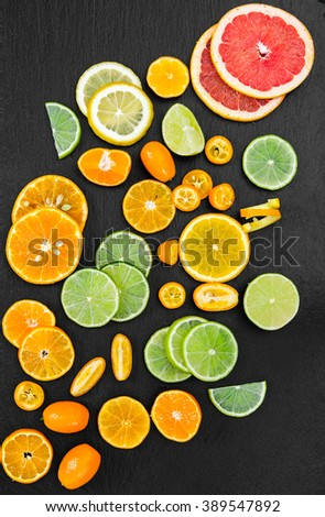 Citrus - grapefruit, orange, tangerine, lemon, lime and kumquat on black background. Top view. - stock photo