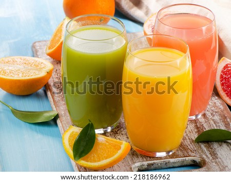 Citrus juice and fruits  on wooden background. Selective focus - stock photo