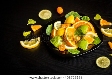 Citrus salad on black background. Slices citrus fruits. Top view - stock photo