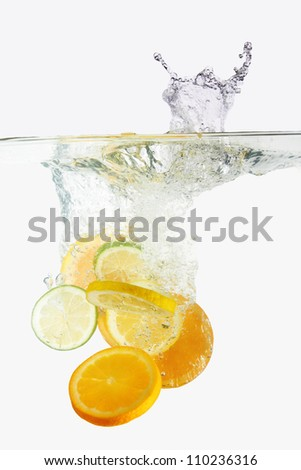Citruses dropped into water with splash on white - stock photo
