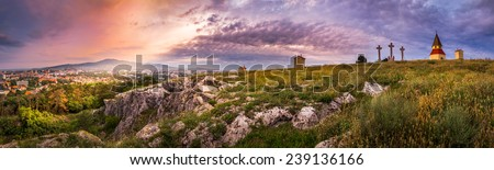 City and Village under a Hill at Sunset as Seen from Calvary, Nitra, Slovakia. Meadow with Flowers and Rocks in Foreground. - stock photo