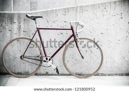 City bicycle fixed gear and concrete wall, vintage old retro bike, cycling or commuting in city urban environment, ecological transportation concept - stock photo