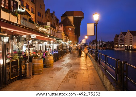 City break in Old Town of Gdansk by night in Poland, Europe, riverside promenade (Dlugie Pobrzeze street) with cafes, restaurants, view towards The Crane