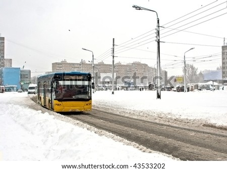 City bus moving on winter road - stock photo