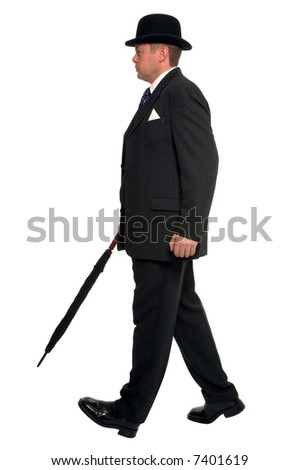 City businessman in pin striped suit wearing a bowler hat and carrying an umbrella as he walks along. - stock photo