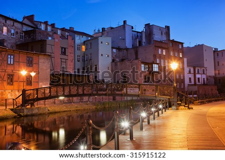 City Bydgoszcz in Poland by night, old town houses with footbridge over Mlynowka river and Mill Island boardwalk alley.