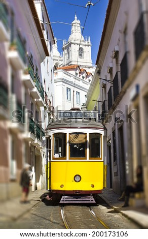 City center of Lisbon, Portugal. Colorful yellow tram with a pittoresque white church in the background.  - stock photo