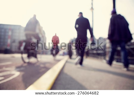 City commuters. High key blurred image of people riding a bike in the street. Unrecognizable faces.