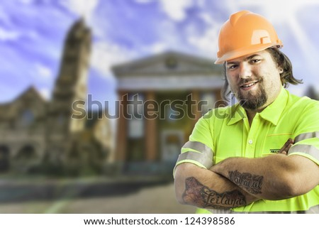 City construction worker arms crossed, tattooed with blurred city buildings behind him - stock photo