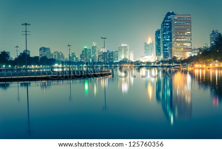 City downtown at night with reflection of skyline,Blue green tone - stock photo