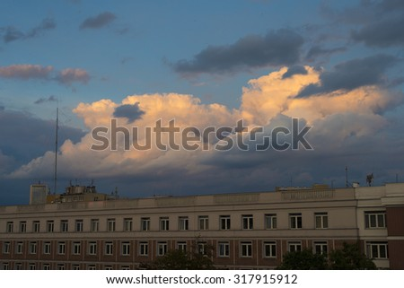 city evening scene with big building top and dramatic sky