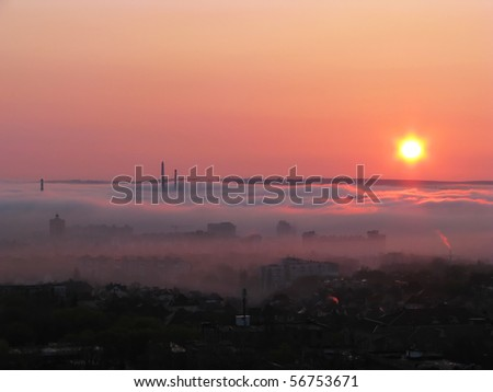 City in the morning fog.  Birdâ??s-eve view to the foggy town in the early morning. - stock photo