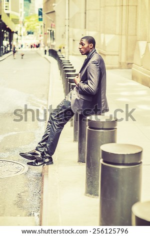 City Life. Young black college student sitting on street, hunchbacked, sad, tired, thinking, lost in thought. Concept of teenagers questioning life, career, self esteem. Retro filtered look. - stock photo
