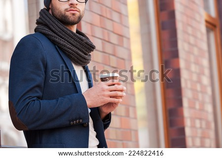 City lifestyle. Cropped image of handsome young man in smart casual wear holding coffee cup while standing outdoors  - stock photo