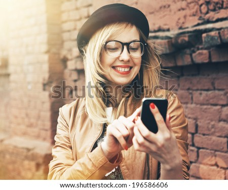 City lifestyle stylish hipster girl using a phone texting on smartphone app in a street - stock photo