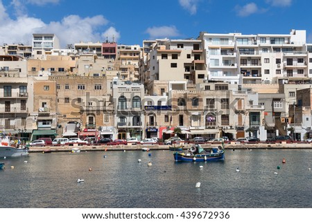 City Marsascala, island Malta, May 02, 2016 Bay in the city Marsascala (Marsaskala),with a path lining the water of Mediterranean sea in the background. Shops and residential houses. Cloudy sky.