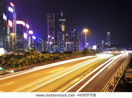 City Night. Hong Kong. Corporate building at the back and busy traffic across the main road at rush hour.