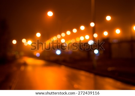 City night lights, road bridge with the lights in the fog after rain. Defocused image, in yellow tones - stock photo
