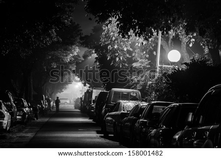City night with cars parked at small lane and one man walk alone, shot at Taipei, Taiwan, Asia. - stock photo