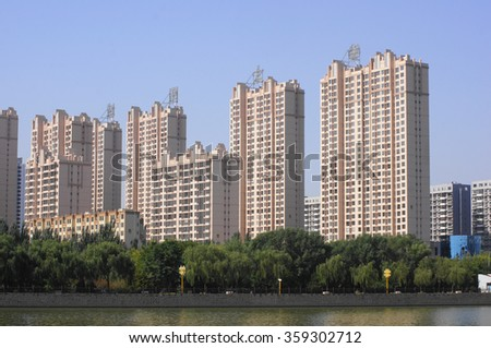 City of Datong (Shanxi, China). Housing development. New high-rise apartment buildings on the bank of pound. Sunny autumn day of October 04, 2015. People's Republic of China. - stock photo