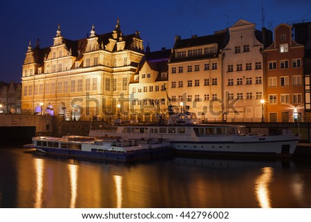 City of Gdansk by night in Poland, Green Gate and historic houses, passenger boats on Motlawa River - stock photo