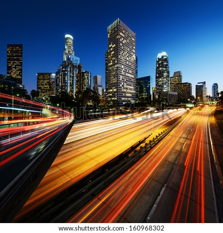 City of Los Angeles California at sunset with light trails - stock photo