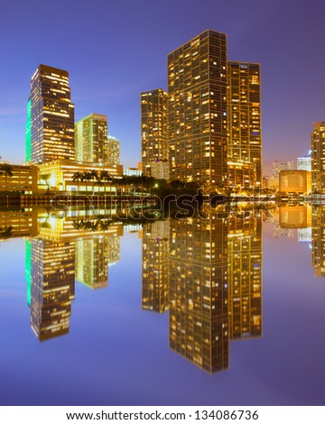 City of Miami Florida, night skyline. Cityscape of residential and business buildings lit by bright lights after sunset with reflections - stock photo