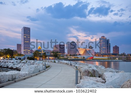 City of Milwaukee skyline. Image of Milwaukee skyline at twilight with city reflection in lake Michigan and harbor pier. - stock photo