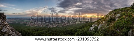 City of Nitra from Above at Sunset with Rocks and Plants in Foreground as Seen from Zobor Mountain - stock photo