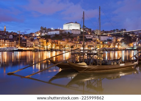 City of Porto at night in Portugal. Rabelo traditional Portuguese cargo boats with wine barrels on Douro river and old city skyline. - stock photo
