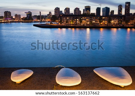 City of Rotterdam skyline at twilight and promenade along the river with illuminated benches, South Holland, the Netherlands. - stock photo