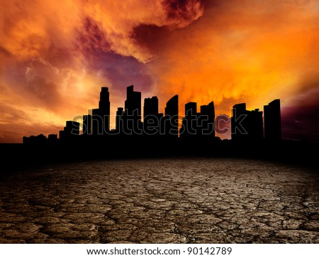 City overlooking desolate desert landscape with cracked earth - stock photo