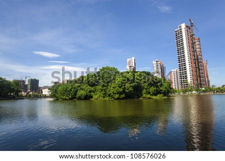 City park with a small forest island reflection and constructed high multi-story apartments near a city lake
