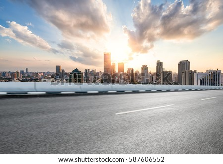 city road with cityscape and skyline of shanghai financial district at sunset.