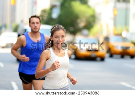City runners - urban new yorkers people running in busy street in New York NYC. Young adults asian caucasian jogging in traffic on Manhattan during summer. - stock photo