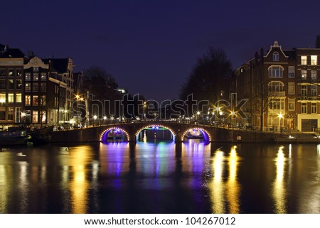City scenic from Amsterdam by night at the river Amstel in the Nethrlands - stock photo