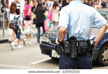 city security. policeman watching order in the urban street  - stock photo