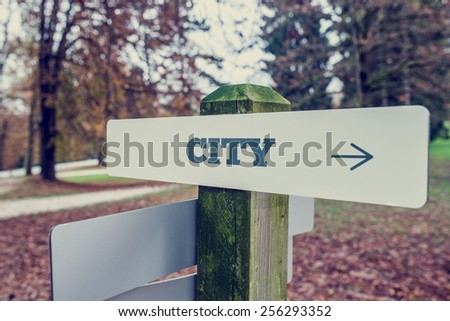 City signpost with right pointing arrow and text on a rustic wooden pole in woodland with a faded retro effect. - stock photo