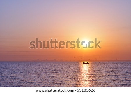 city silhouette from sea at sunrise - stock photo